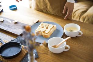 ピーナツバターとバナナの甘いスイーツトーストを料理する女性のイメージ写真の写真素材 [FYI04671224]