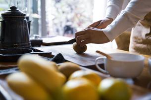 キウイフルーツを包丁で切り、調理する女性の手元の写真素材 [FYI04671227]