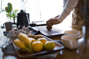 キウイフルーツを包丁で切り、調理する女性の手元の写真素材 [FYI04671229]