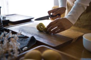 キウイフルーツを包丁で切り、調理する女性の手元の写真素材 [FYI04671231]