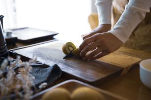 キウイフルーツを包丁で切り、調理する女性の手元の写真素材 [FYI04671232]