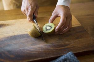 キウイフルーツを包丁で切り、調理する女性の手元の写真素材 [FYI04671233]