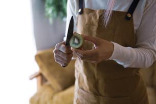 キウイフルーツを包丁で切り、調理する女性の手元の写真素材 [FYI04671235]
