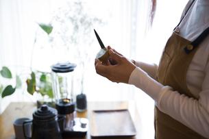 キウイフルーツを包丁で切り、調理する女性の手元の写真素材 [FYI04671236]