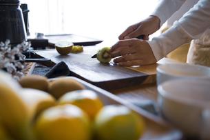キウイフルーツを包丁で切り、調理する女性の手元の写真素材 [FYI04671240]