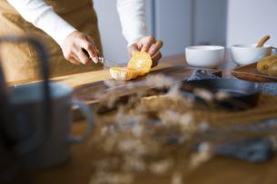 みかんを包丁で切り、調理する女性の手元の写真素材 [FYI04671244]