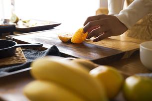 みかんを包丁で切り、調理する女性の手元の写真素材 [FYI04671246]