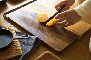 みかんを包丁で切り、調理する女性の手元の写真素材 [FYI04671247]