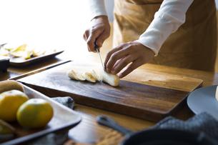 バナナをを包丁で切り、調理する女性の手元の写真素材 [FYI04671248]
