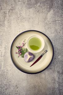 丸い皿に置かれたお茶と和菓子の写真素材 [FYI04671551]