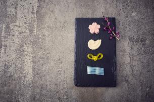 黒い石板に置かれ和菓子と枝の写真素材 [FYI04671553]