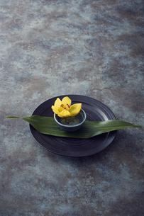 黒い皿に敷かれた葉っぱと小皿に活けられた黄色い花の写真素材 [FYI04671566]
