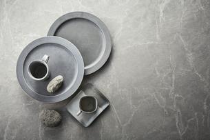 グレーのバック素材の上の皿とカップと石の写真素材 [FYI04671583]