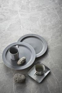 グレーのバック素材の上の皿とカップと石の写真素材 [FYI04671584]