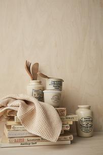 ベージュトーンでまとめた本と布巾とキッチン雑貨の写真素材 [FYI04671607]