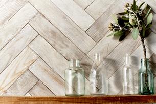 木の棚に置かれたガラス瓶と生けられた植物の写真素材 [FYI04671725]