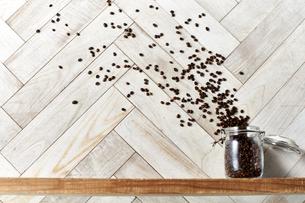 木の棚に置いたキャニスターから放たれるコーヒー豆の写真素材 [FYI04671736]