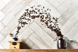 木の棚に置いたキャニスターからミルに放たれるコーヒー豆の写真素材 [FYI04671738]