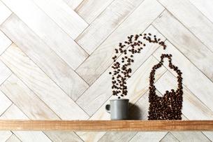 木の棚に出来たコーヒー豆のボトルからカップに放たれる豆の写真素材 [FYI04671744]