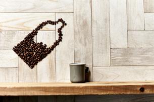 木の棚に置かれたカップに傾くコーヒー豆で出来たボトルの写真素材 [FYI04671747]