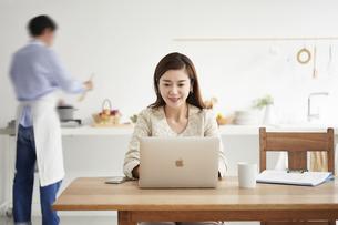 自宅でパソコンを開き仕事をする女性と料理をする男性の写真素材 [FYI04671773]