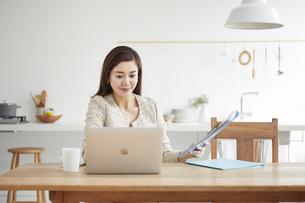 自宅でパソコンを開き仕事をする女性の写真素材 [FYI04671774]