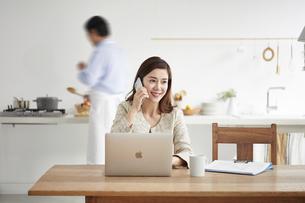 自宅でパソコンを開き仕事をする女性と料理をする男性の写真素材 [FYI04671780]