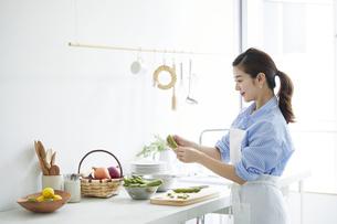 キッチンで料理を作る女性の写真素材 [FYI04671781]