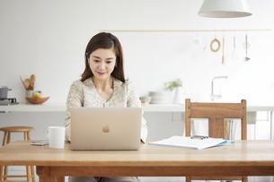 自宅でパソコンを開き仕事をする女性の写真素材 [FYI04671783]