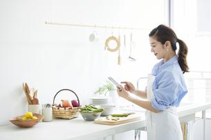 キッチンで料理を作る女性の写真素材 [FYI04671785]