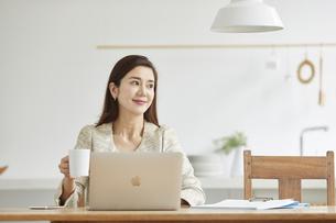 自宅でパソコンを開き仕事をする女性の写真素材 [FYI04671787]