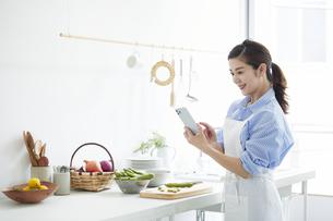 キッチンで料理を作りながらスマホを見る女性の写真素材 [FYI04671789]