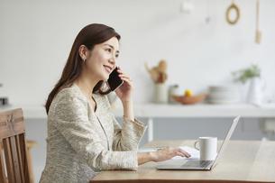 自宅でパソコンを開き仕事をする女性の写真素材 [FYI04671790]