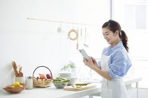 キッチンで料理を作りながらスマホを見る女性の写真素材 [FYI04671793]