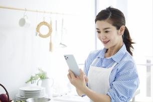 キッチンで料理を作りながらスマホを見る女性の写真素材 [FYI04671802]