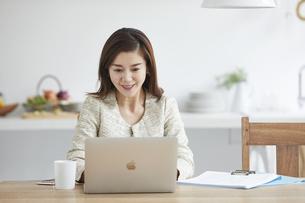 自宅でパソコンを開き仕事をする女性の写真素材 [FYI04671807]