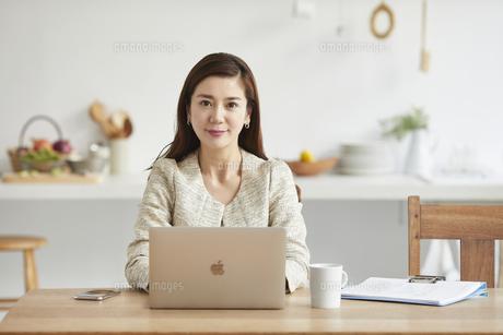 自宅でパソコンを開き仕事をする女性の写真素材 [FYI04671808]