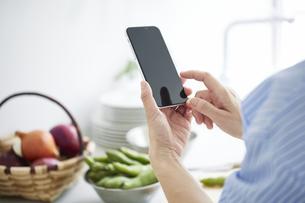 キッチンで料理を作りながらスマホを見る女性の写真素材 [FYI04671810]