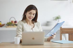 自宅でパソコンを開き仕事をする女性の写真素材 [FYI04671814]