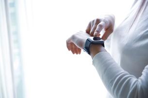 白い背景とスマートウォッチ操作する、白い服の女性の手元の写真素材 [FYI04671826]