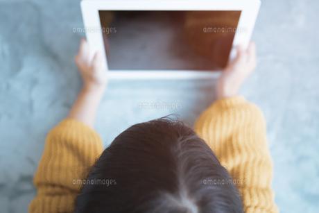 部屋でタブレットPCで画面を見るこどもの写真素材の写真素材 [FYI04671844]