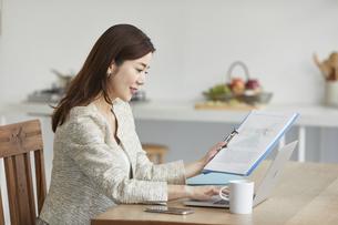 自宅でパソコンを開き仕事をする女性の写真素材 [FYI04671852]