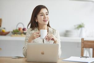 自宅でパソコンを開き仕事をする女性の写真素材 [FYI04671856]