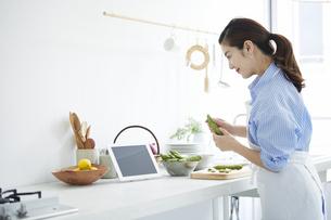 キッチンでタブレットPCを見ながら料理を作る女性の写真素材 [FYI04671863]