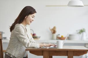 自宅でパソコンを開き仕事をする女性の写真素材 [FYI04671868]