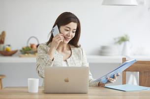 自宅でパソコンを開き仕事をする女性の写真素材 [FYI04671872]
