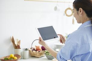 キッチンでタブレットPCを見ながら料理を作る女性の写真素材 [FYI04671874]