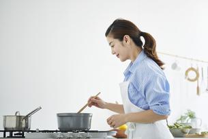 キッチンで料理を作る女性の写真素材 [FYI04671879]