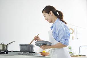 キッチンで料理を作る女性の写真素材 [FYI04671886]
