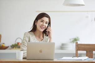 自宅でパソコンを開き仕事をする女性の写真素材 [FYI04671888]